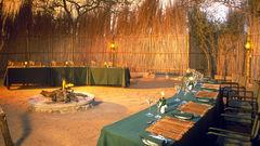 I boman serveras middagen under stjärnorna runt en dånande lägereld.