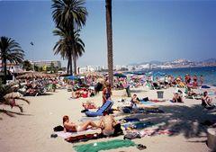 Den här 2,7 km långa sandstranden på Ibiza lockar både barnfamiljer, vattensportare och partymänniskor.